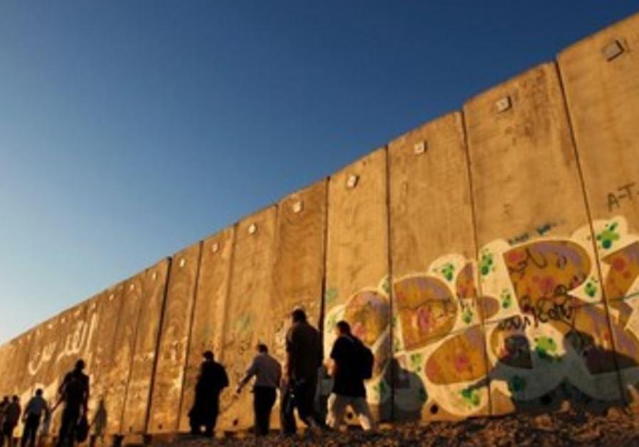 Palestinian men walk by Qalandiya checkpoint.