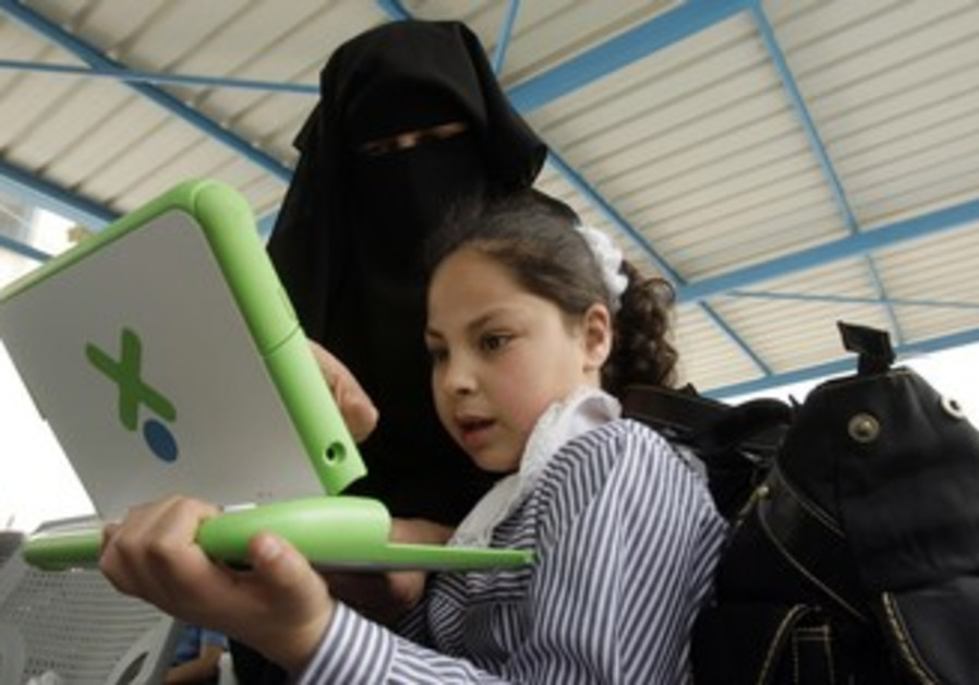 Gaza teacher shows a girl how to use computer