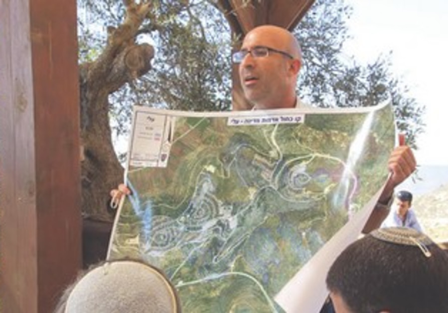 Koby Elraz shows map of his settlement