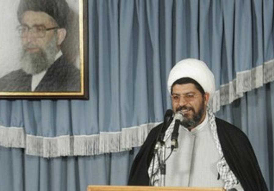 Ali Shirazi speaks under picture of Ayatollah.