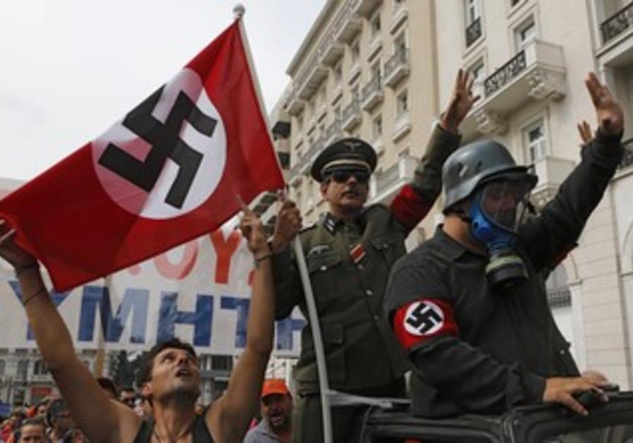 Greeks wave swastikas to greet Merkel