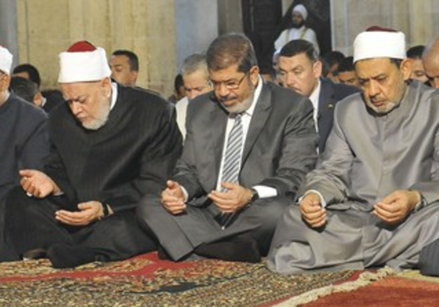 MOHAMED MORSI, center, prays at Al-Azhar mosque in