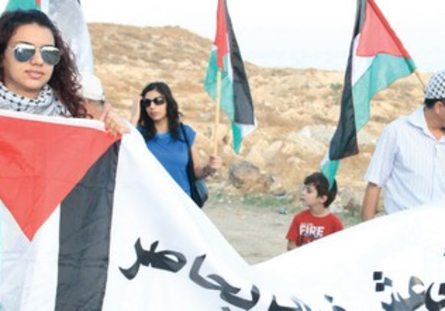 PROTESTERS CARRY a banner in Gush Etzion