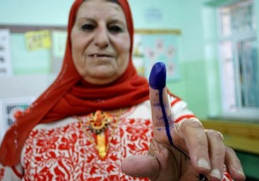 A Palestinian woman votes