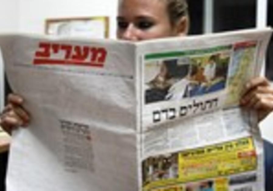 Woman reads Ma'ariv newspaper