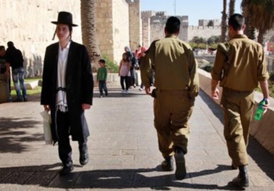 Haredi man and IDF soldiers walk in Jerusalem