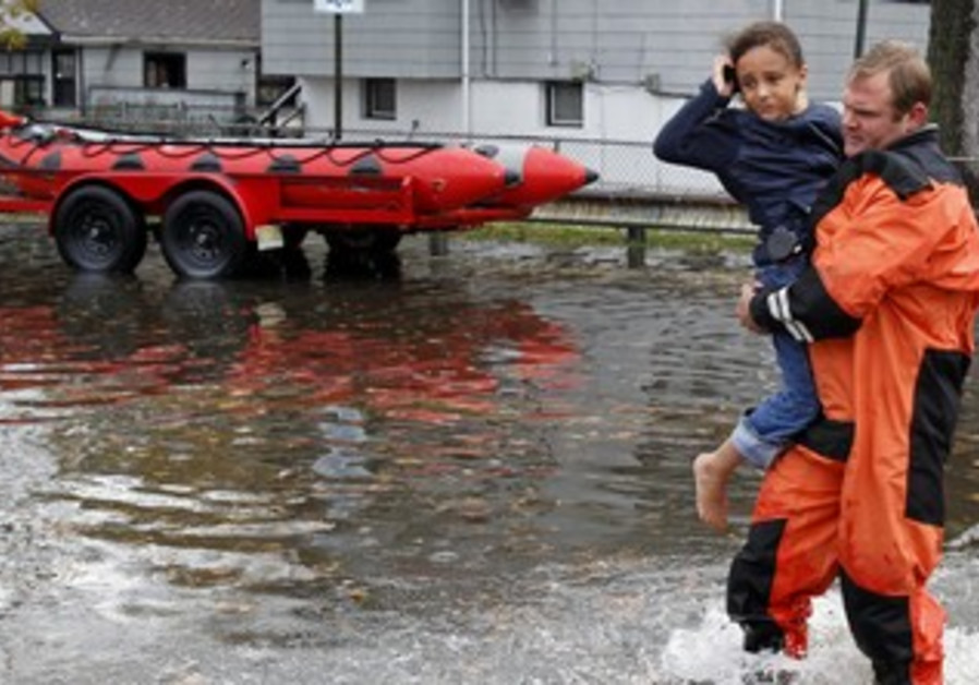 Rescue worker carries girl out of flood waters