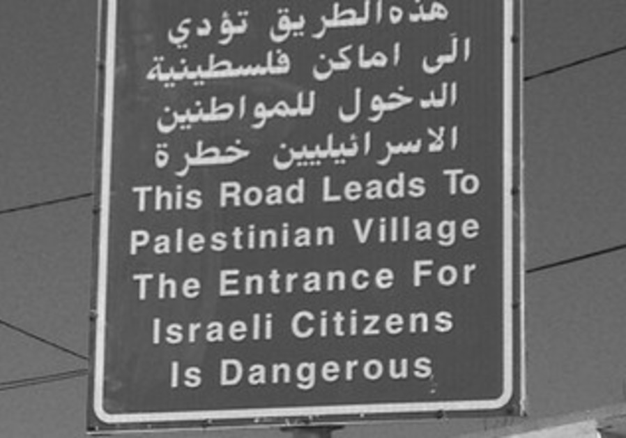 A LARGE red sign declares entry forbidden to Israe