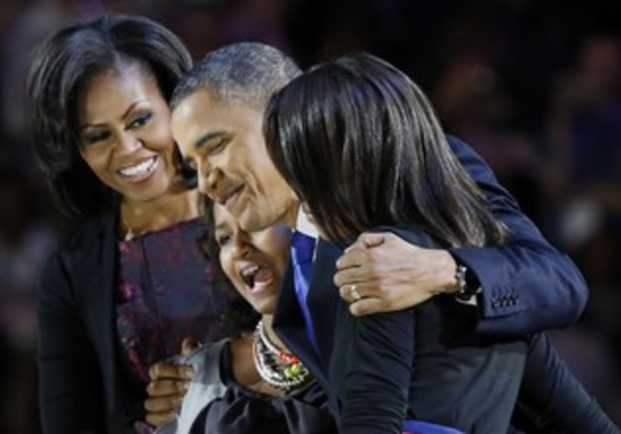 Obama hugs his family after winning re-election