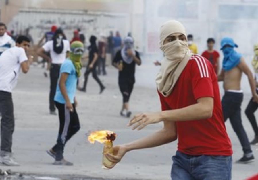 A SHI'A anti-government protester throws a Molotov