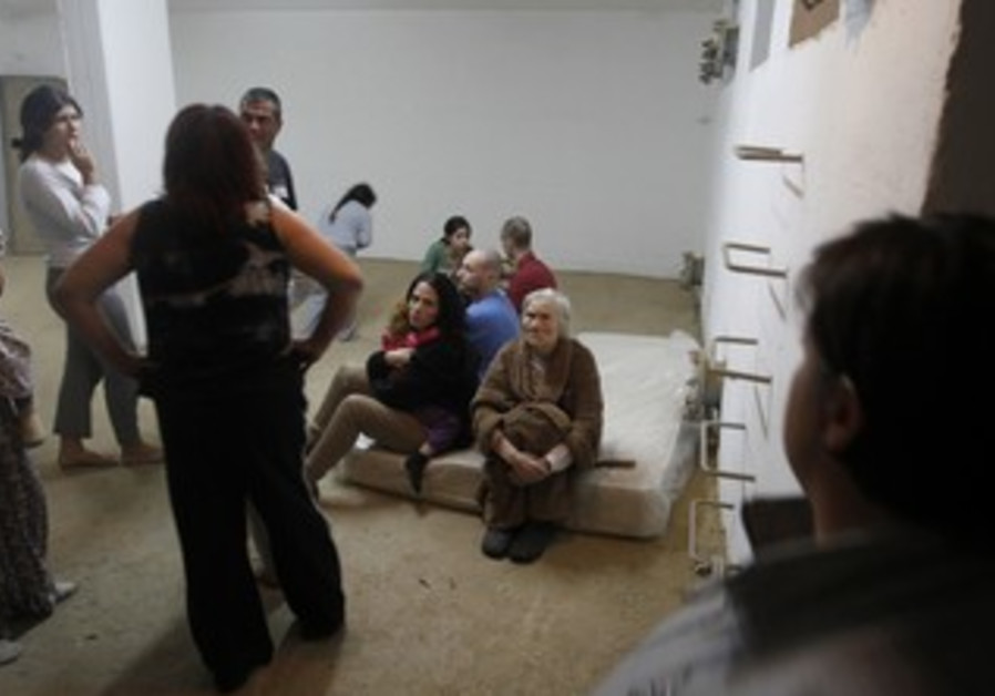 Israelis in Beersheba sit in a bomb shelter
