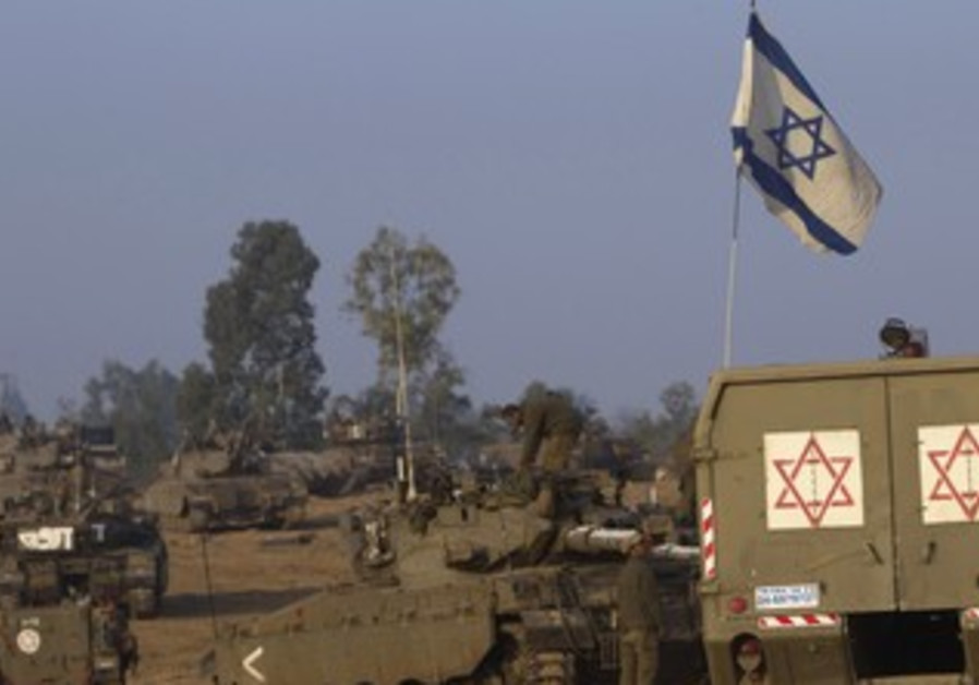 IDF tanks and a flag on the Gaza border