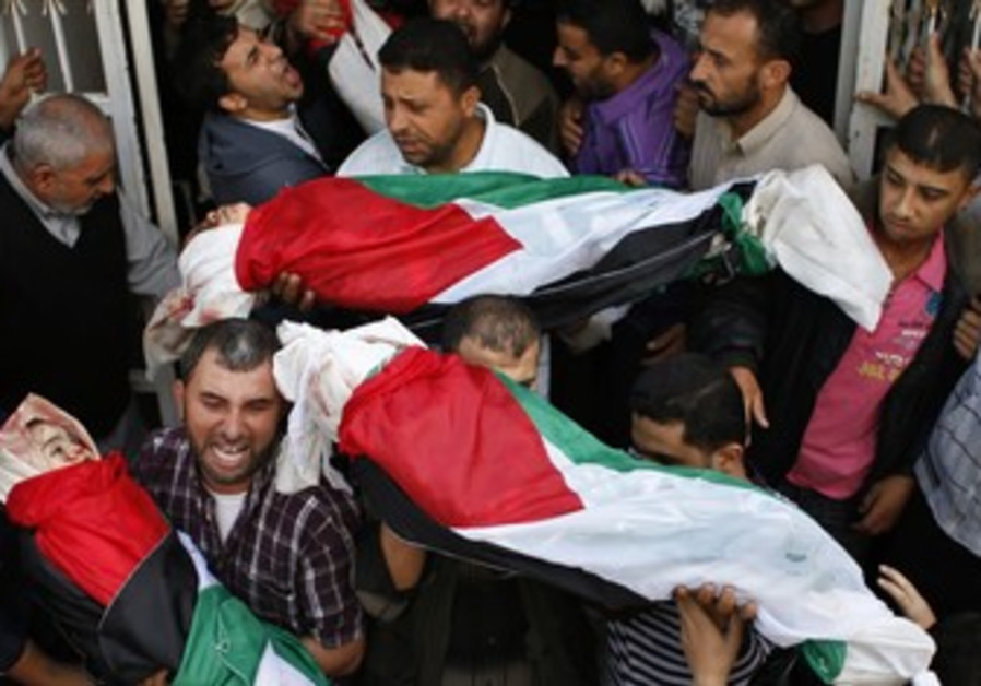 Palestinians carry the bodies of four siblings