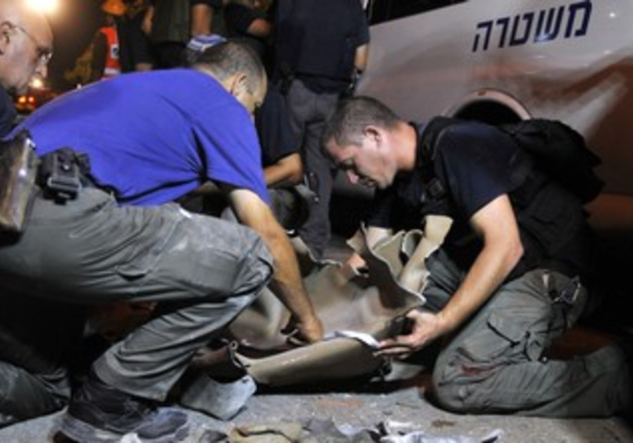Police sappers gather parts of rocket in Rishon