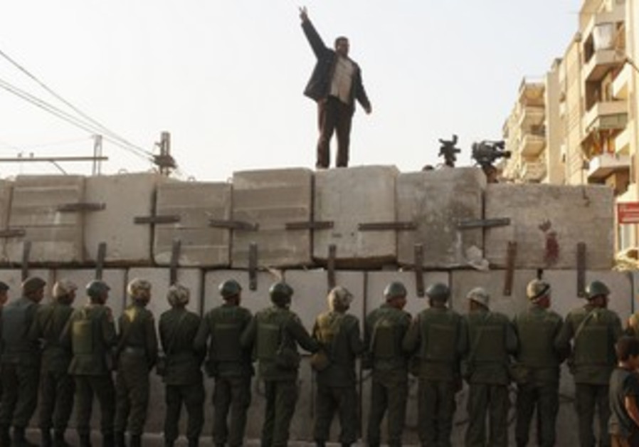 Egyptian protester on barrier surrounding palace