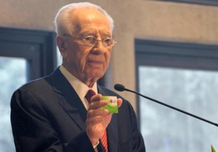 President Peres holding ADI card.