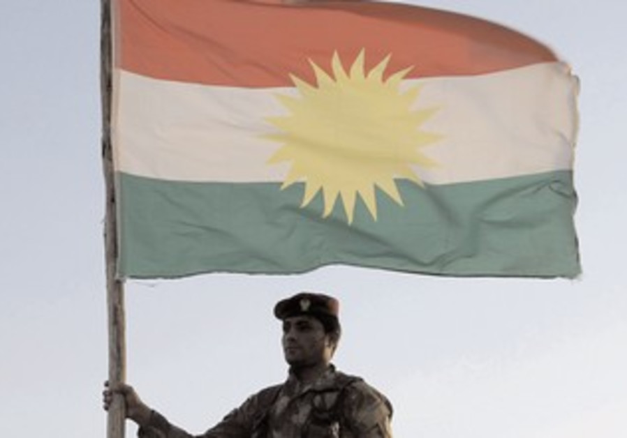 Kurdish soldier holding flag.