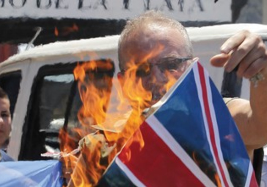 A protester burns the UK flag in Argentina