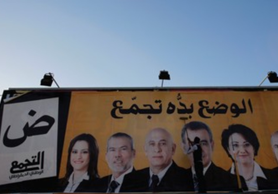 A WORKER puts up a campaign poster for Balad