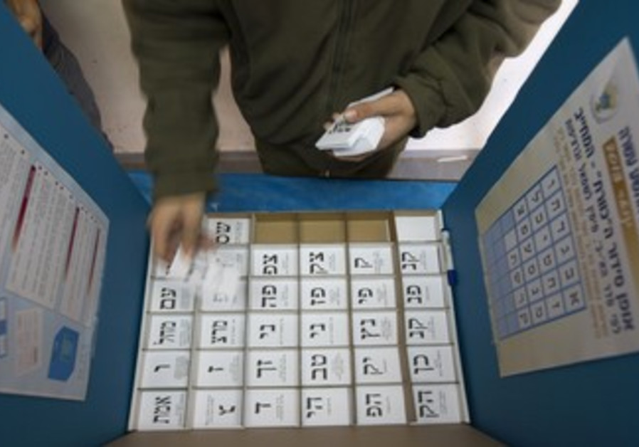 An Israeli arranges ballots in a voting booth
