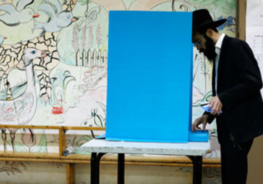 An ultra-Orthodox Israeli casts his vote at a polling station in the settlement of Kocha Yaacov.