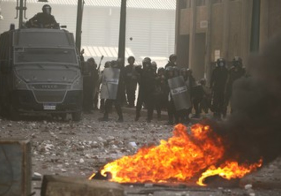 Police throw stones at protesters during clashes in Alexandria, Egypt January 25, 2013.