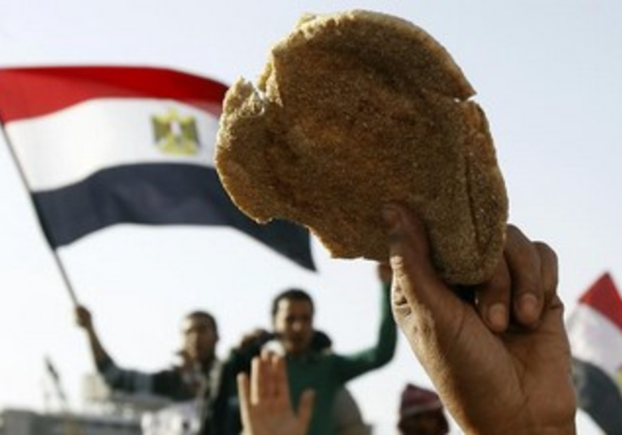 Egyptian holds a loaf of bread in Tahrir, February 8, 2013