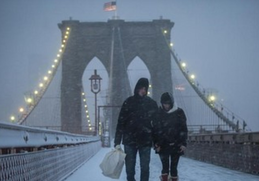A couple makes their way across the Brooklyn Bridge through snow and wind in New York, February 8