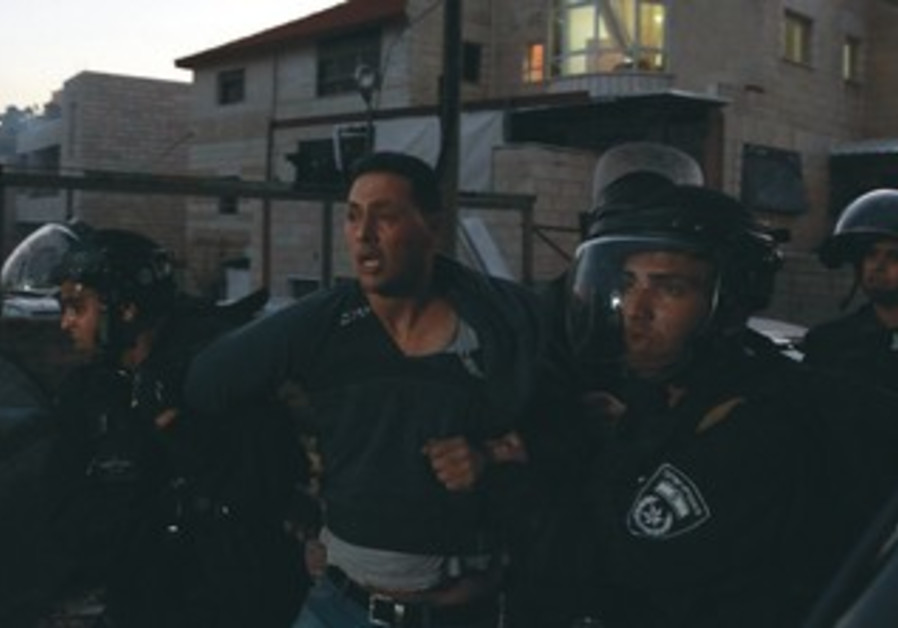 PALESTINIAN SUSPECTED of throwing stones is detained by security personnel during clashes in J'lem