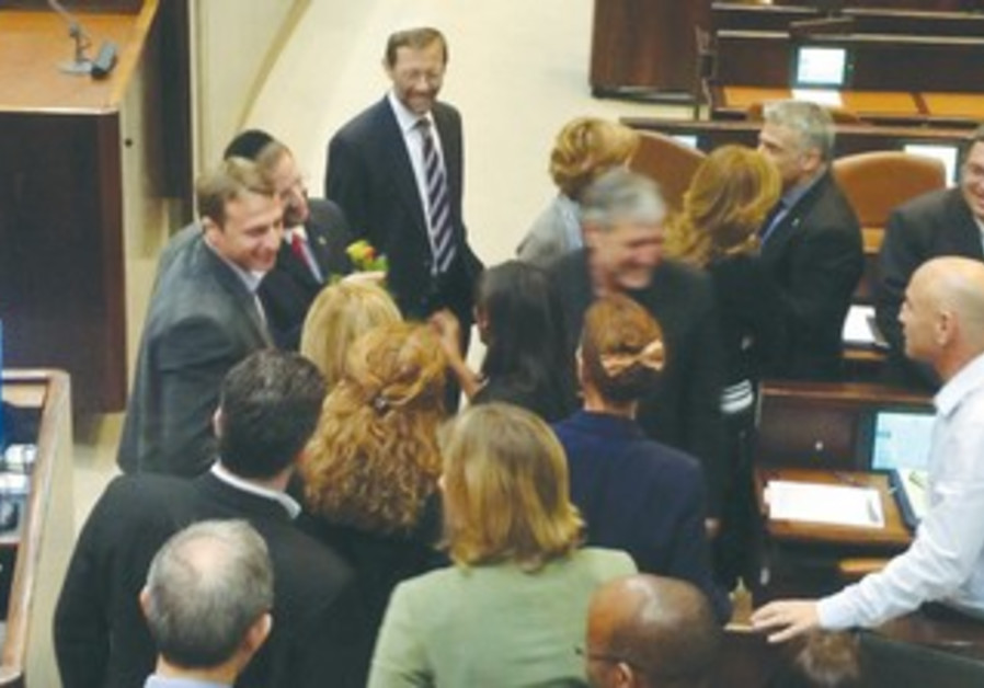 FEMALE YESH ATID MKs hand flowers to MK Dov Lipman (left) following his inaugural Knesset speech