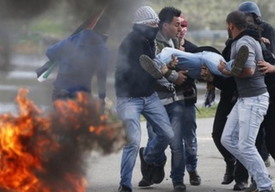 Stone-throwing Palestinian protesters carry a protester injured by IDF outside Ofer Prison, Feb 15