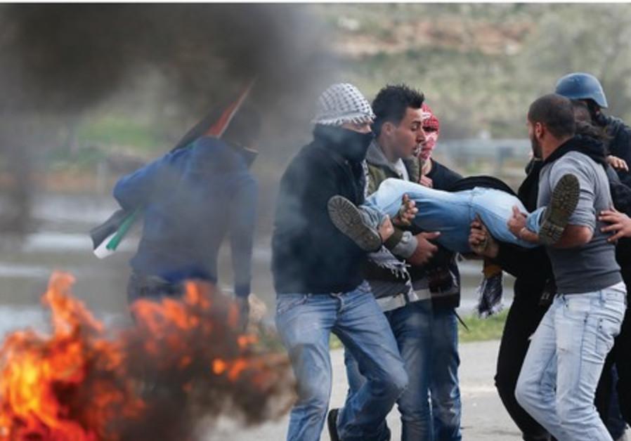 Palestiniens portant un blessé après une confrontation avec les forces de sécurité.