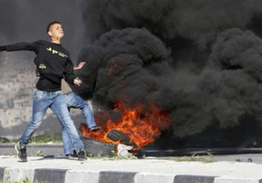 A Palestinian throws a stone at IDF soldiers during clashes at Hawara, February 20, 2013