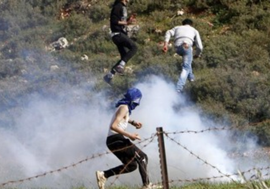 Stone-throwing Palestinian protesters run away from tear gas fired by Israeli security forces