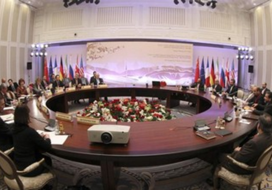 Participants sit at a table during talks on Iran's nuclear program in Almaty