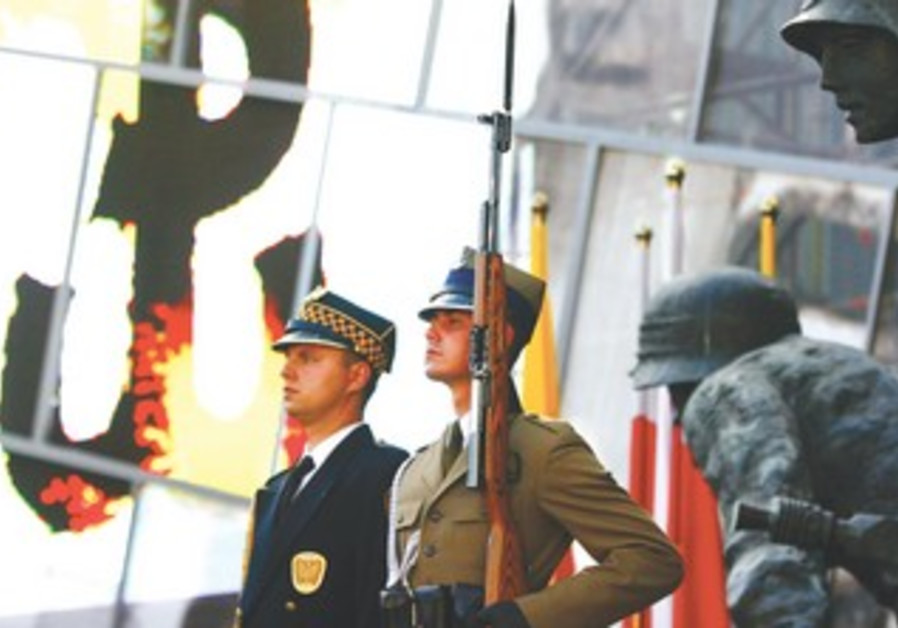 GUARDS STAND at a memorial commemorating the 64th anniversary of the Polish uprising against Nazis