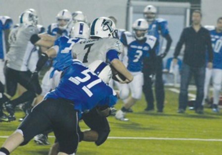 TEL AVIV PIONEERS defender Yotam Anticovich (57) takes down Hasharon Hammers quarterback