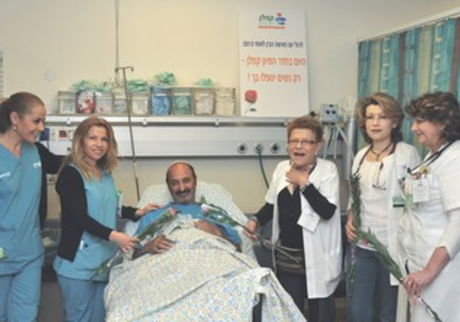 ZOHAR KATUA smiles between female medical staffers at the Rehovot hospital yesterday.