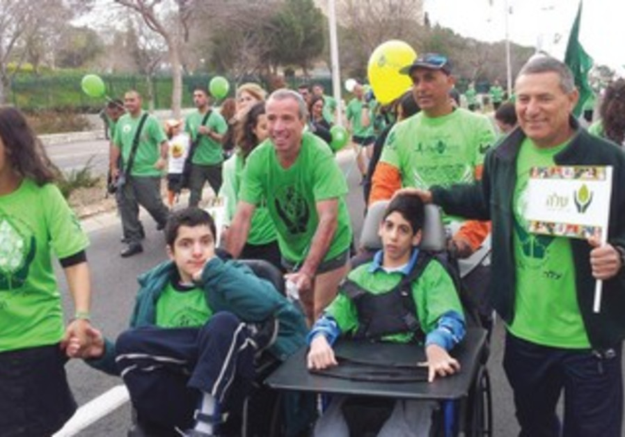 DORON ALMOG (with pennant) and MK Elazar Stern with Aleh youngsters pose at the Jerusalem Marathon.