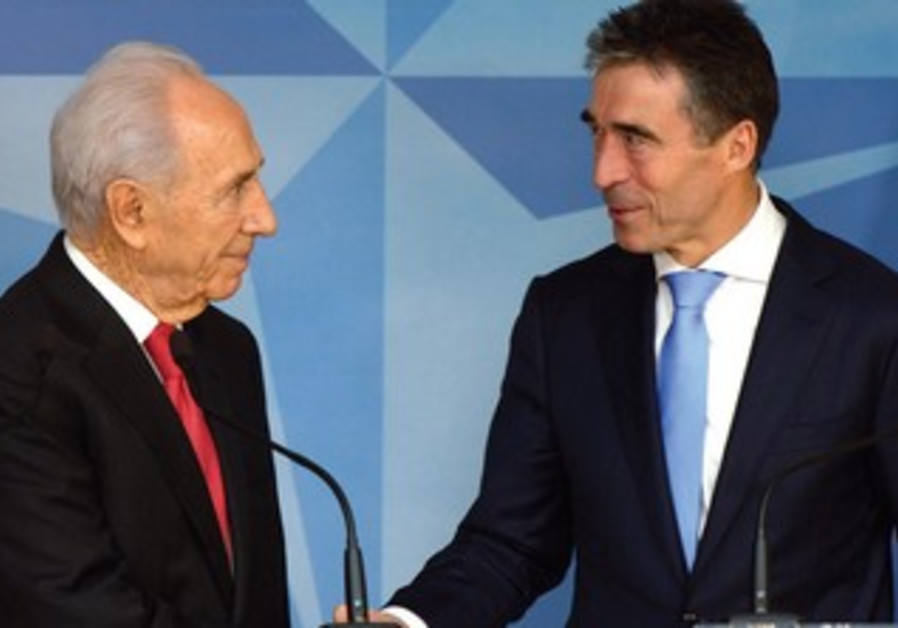 PRESIDENT SHIMON PERES shakes hands with NATO Secretary-General Anders Fogh Rasmussen at NATO HQ