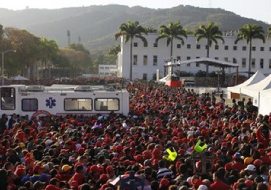 Supporters of Venezuela's late President Hugo Chavez gather as they wait for a chance to view body