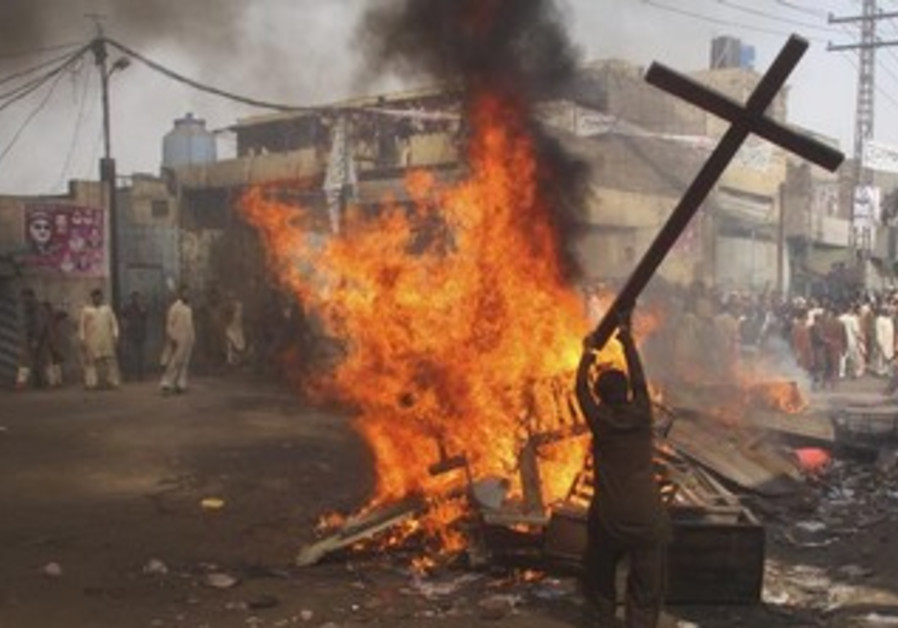 A demonstrator burns a cross during a protest in the Badami Bagh area of Lahore March 9, 2013.
