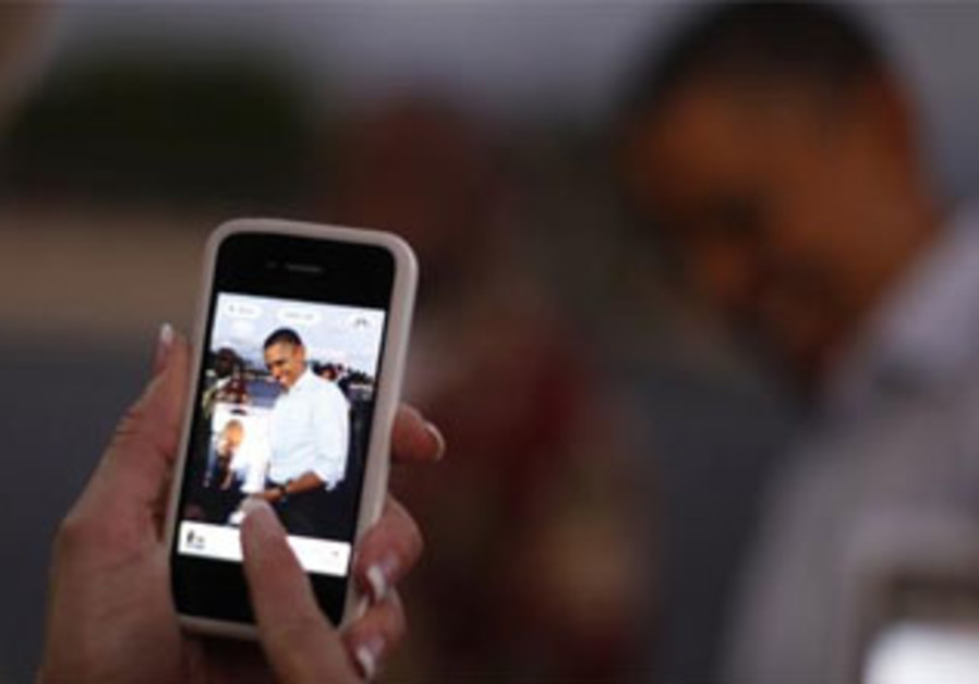 A woman snaps a picture of U.S. President Barack Obama with her iPhone in Hawaii, December 2011.