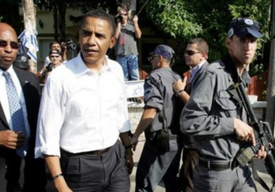 Senator Barack Obama is escorted by an Israeli police officer in Sderot July 23, 2008