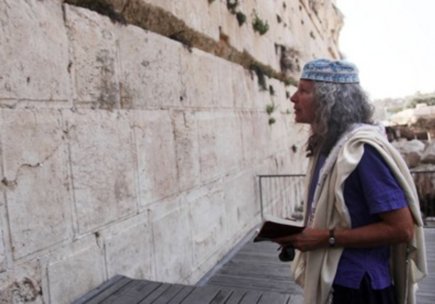 A woman wearing a prayer shawl prays at the Western Wall
