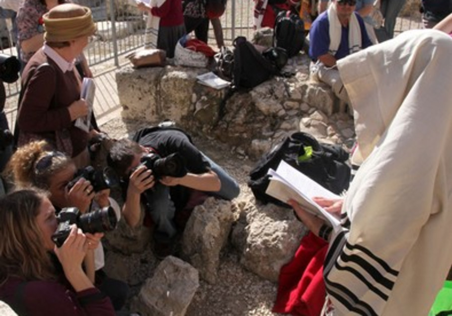 Photographers taking pictures of woman in prayer shawl at the Western Wall
