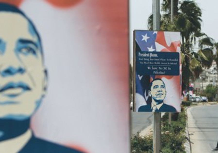 A MAN in Ramallah walks past signs depicting US President Barack Obama, March 12