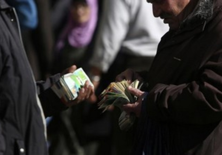 Palestinian money changes exchange money [file].
