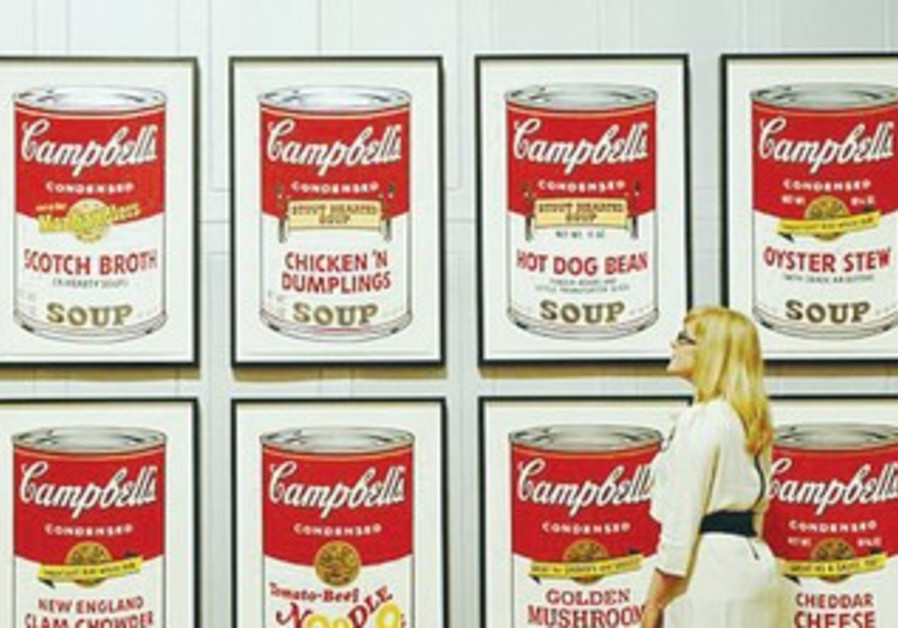 A DULWICH Picture Gallery employee poses next to Andy Warhol's 1969 'Campbell Soup II,' in London la