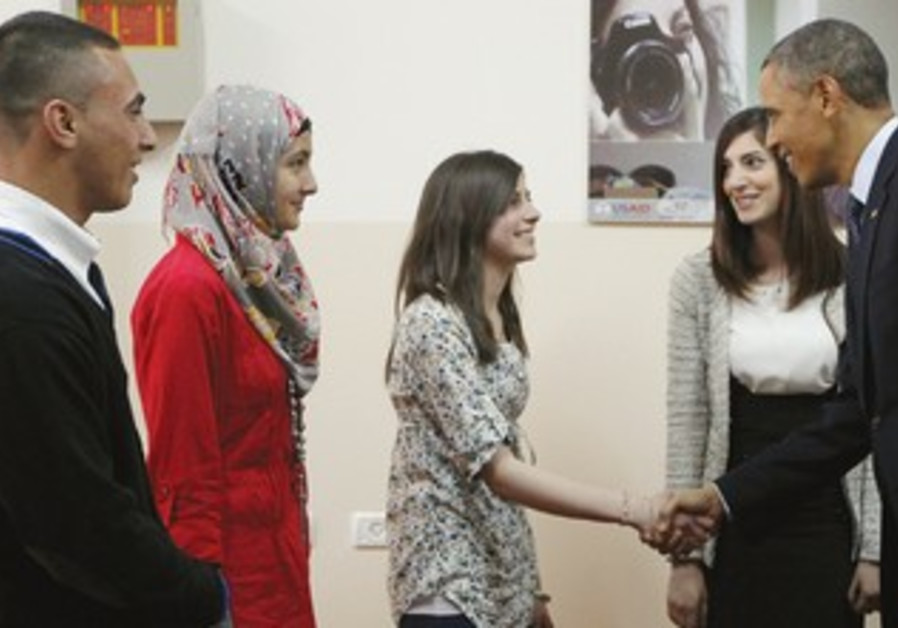 Obama shakes hands with a Palestinian teen during his visit to the Bireh Youth Center in Ramallah